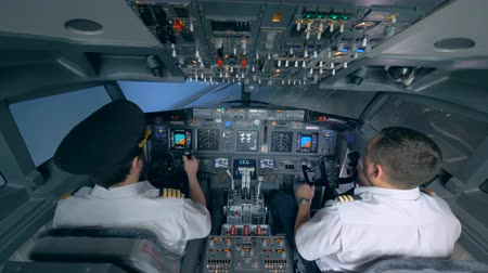 pilot in command : Two pilots turn the plane in a flight simulator.