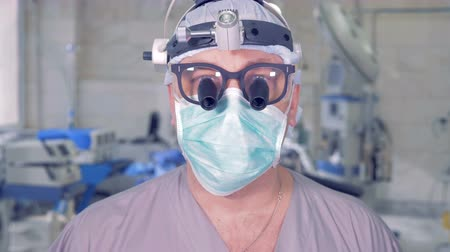 surgical equipment : Professional doctor lifting his head up and staring intently into the camera