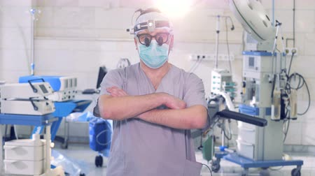 ekli : Male professional surgeon is walking and stopping in front of a camera while looking directly into it