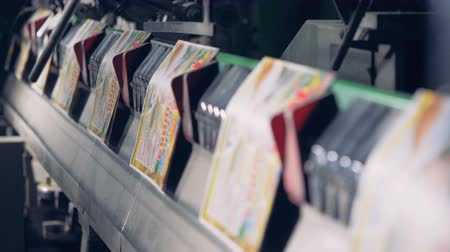 nakladatelství : A row of colourful printed cards moving along the conveyor belt Dostupné videozáznamy
