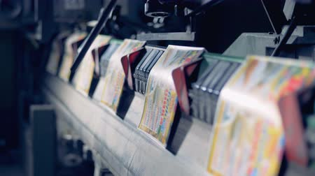 fix : Close up of printed cover pages moving along the conveyor