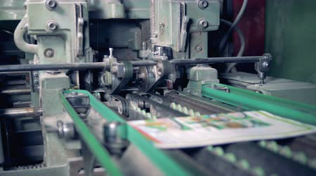 unready : An industrial machine is cutting off edges of printed magazines