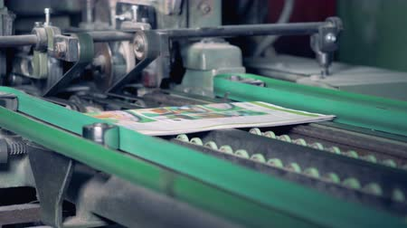 nakladatelství : Colourful printed newspapers are getting their edges cut off by a factory mechanism