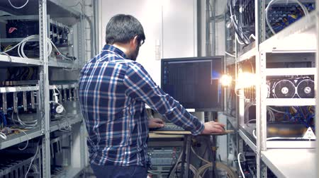 mining farm : Backside view of an adult man working in a mining rig Stock Footage