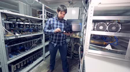 unit : Male programmer is standing in the middle of a mining farm unit with a keyboard and working