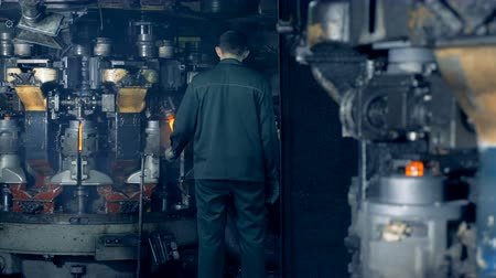 scrutiny : A worker watches how special machine melts out bottles at a plant. 4K.