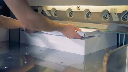 nastavení : A stack of formsheets is being added to the other pile of paper and they are moved under a cutter by the man