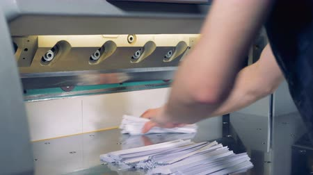 trimmings : Cutter is shearing extra edges of paper sheets thereafter the man is moving everything away Stock Footage