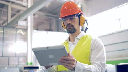 supervisor : A man works on his tablet at a industrial facility, close up. Stock Footage