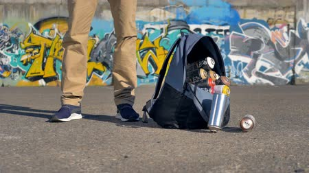 ghetto streets : Backpack is getting thrown onto the ground and spray paints are rolling out of it Stock Footage