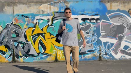 urbanística : Adult graffiti artist is taking a backpack off the ground and leaving the graffiti wall behind
