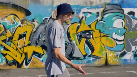 grafiti : Young man is walking along the street with graffiti painting on the background and a spray in his hands