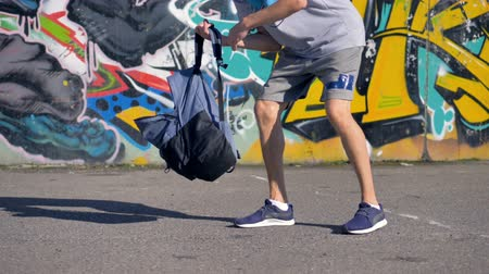 ghetto streets : A young man is putting aerosol barrels with paint into a backpack Stock Footage