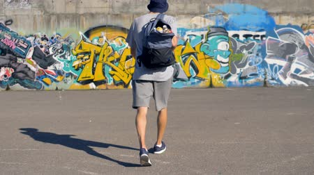 ghetto streets : Graffiti artist is lifting his backpack with paint canisters and going towards the graffiti wall