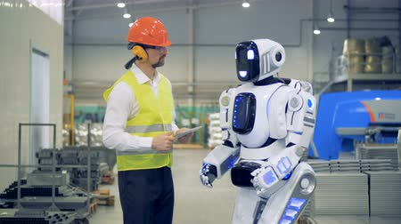 robots : Engineer switches on a robot at a factory. 4K.