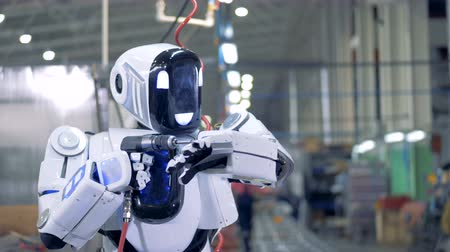 installer : A robot repairs itself, close up. A white robot uses tool to repair itself at a factory.