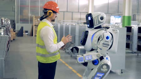 андроид : A man talks to robot at a factory
