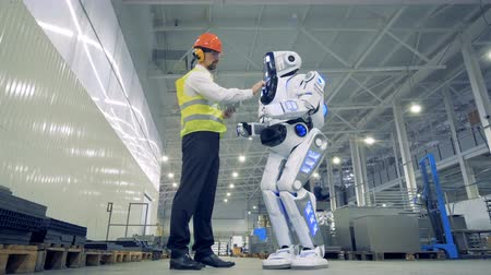 robots : Factory worker switches a robot on, underside view. Stock Footage