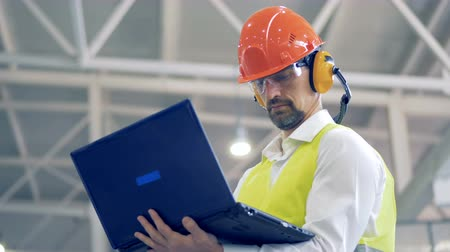 unit : Male factory employee is working with his laptop and glancing around