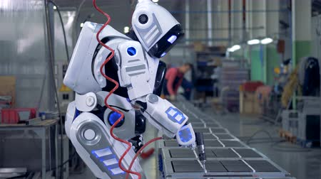 intelligencia : Human-like robot is working with a drill in a factory unit Stock mozgókép