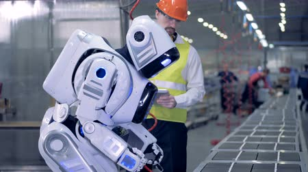 functioning : Human-like robot starts working with a drill after a corresponding command from a factory worker