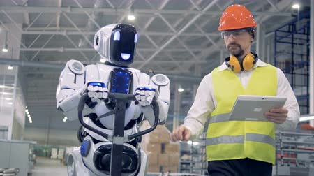 troli : Cyborg is moving a transporting tool along the factory unit while being regulated by a male worker Stock mozgókép
