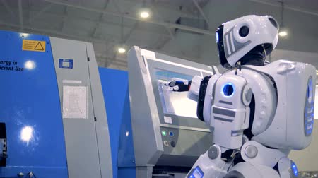 professionalism : Human-like robot is coming to a control panel and setting parameters on a screen