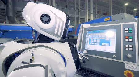 bot : Factory robot is pushing buttons on an electronic touchscreen