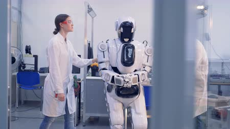 máquina : Human-like cyborg is getting checked and fixed by two engineers