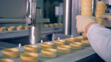 unfilled : Factory worker is putting wafer cups into a moving conveyor belt