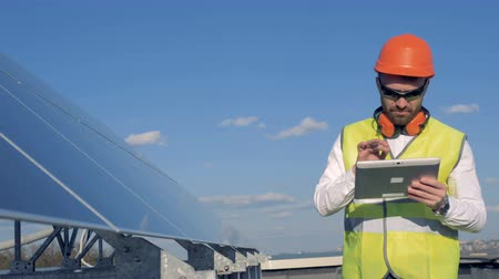 akumulator : Worker looks at solar panels. Wideo