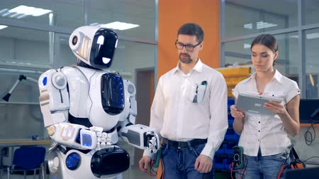 switching : Male engineer is switching a robot on, regulating its hands and instructing a female engineer