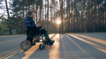 paralympics : Disabled person rides in a wheelchair on the road.