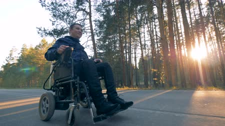 paralympics : A man in wheelchair takes a ride on a forest road.