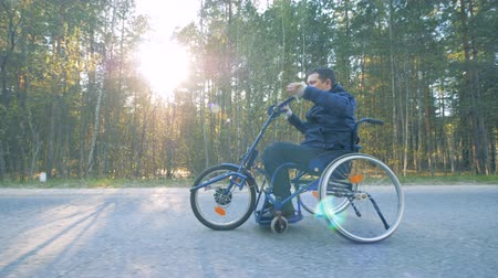 paralympics : Paralyzed patient rides special medical bicycle, side view.