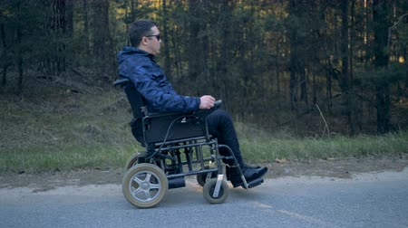 paralympics : Man in a wheelchair enjoys nature, side view.