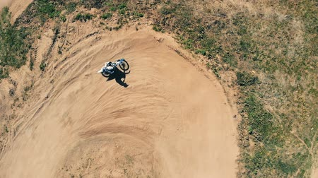 pista de corridas : A sportsman rides on a motorbike, top view.