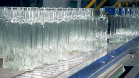 pushed : Empty glass bottles are being pushed onto the conveyor belt Stock Footage