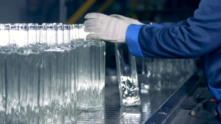identical : Glass-house employee is moving glass bottles along the transporter Stock Footage