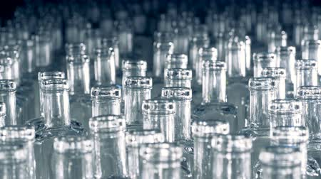 identical : Stack of empty glass bottlings is emerging from darkness