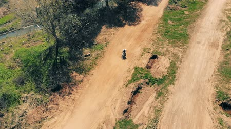 enduro : A biker participates in a motocross, driving near river. 4K.