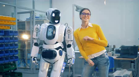 slapping : Young woman is slapping a human-like robot after it spanks her playfully Stock Footage