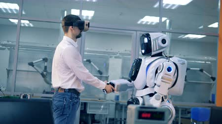 csapatmunka : A human and a human-like android are shaking hands and watching virtual reality