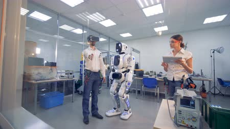 droid : A person with VR glasses tests a robot. Stock Footage
