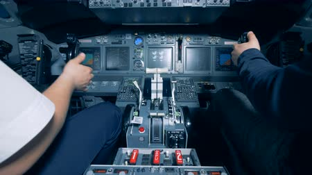 civilní : Two men are sitting in a cockpit of a flight simulator and are operating a flight Dostupné videozáznamy