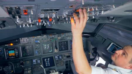 readiness : Airman is switching buttons on the upper side of the cockpit before the flight Stock Footage