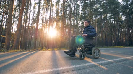 challenged : Disabled man is slowly moving on his powered wheelchair along the alley