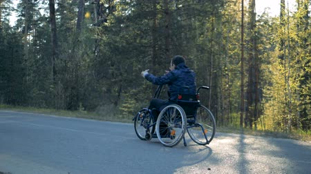 deficientes : Training wheelchair is getting moved along the road by a disabled man Stock Footage