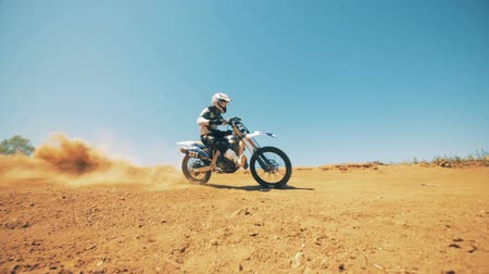 autobike : Motorcyclist is driving his bike through dust and sand in slow motion Stock Footage