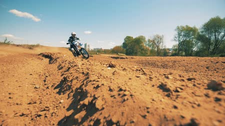 autobike : Slow motion footage of a motorcyclist riding through sandy terrain
